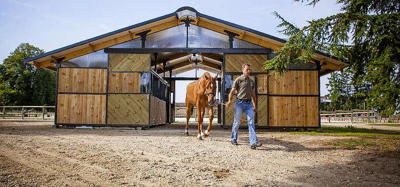 homme sortant un cheval d'une écurie © A. Bassaler